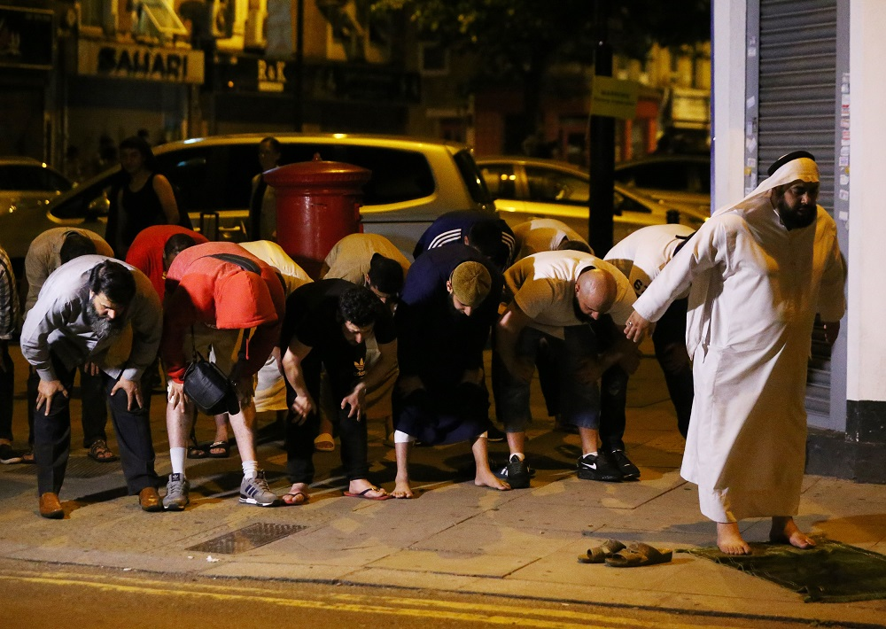 Men pray after a vehicle collided with pedestrians near a mosque in the Finsbury Park neighborhood of North London, Britain June 19, 2017. REUTERS/Neil Hall - RTS17M9D