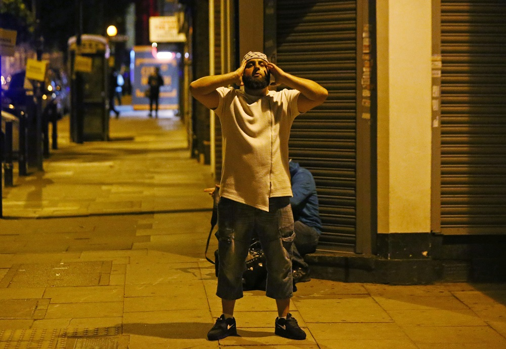 A man prays after a vehicle collided with pedestrians near a mosque in the Finsbury Park neighborhood of North London, Britain June 19, 2017. REUTERS/Neil Hall - RTS17M8T