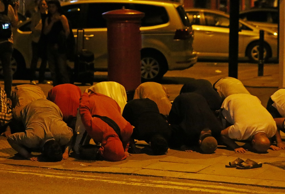 Men pray after a vehicle collided with pedestrians near a mosque in the Finsbury Park neighborhood of North London, Britain June 19, 2017. REUTERS/Neil Hall - RTS17M9C